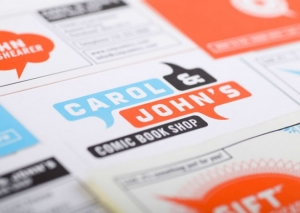 Close-up photo of print identity for Carol & Johns Comic Book Shop by Mikey Burton